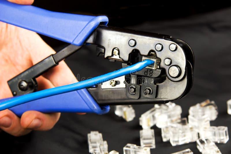 Encrespadura de la mano un conector RJ-45 del par trenzado imagenes de archivo