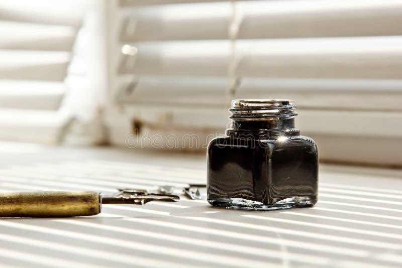 Encrier avec des astuces en m?tal pour le stylo d'encre sur un fond blanc dans les rayons solaires papeterie sur la fin blanche d photo stock