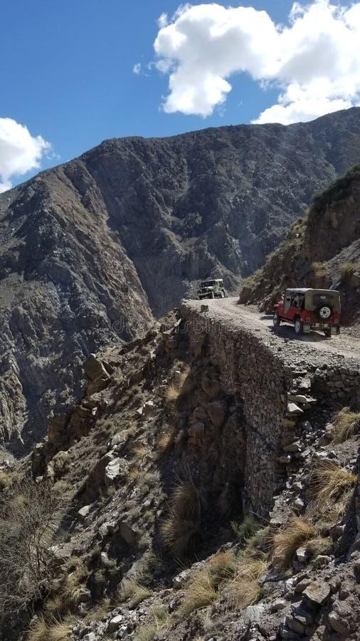 Encuentro campo a través de dos coches en el camino rocoso estrecho con el valle escarpado fotos de archivo libres de regalías