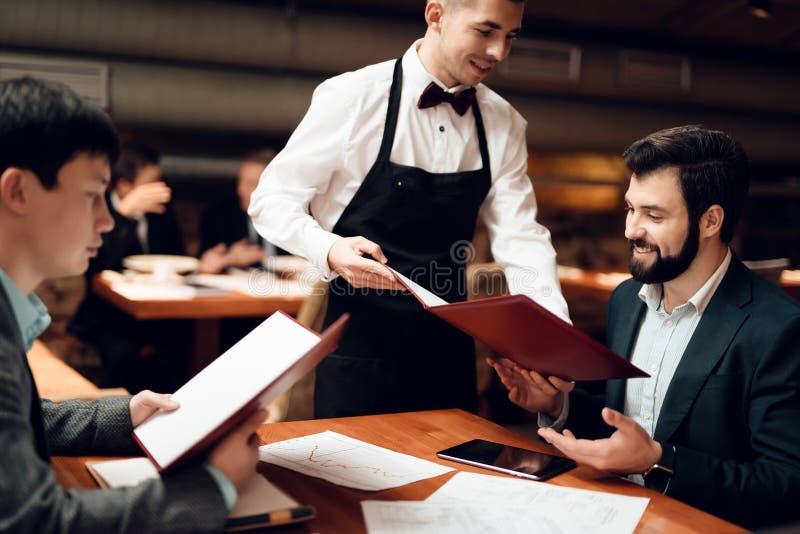 Encuentro con de hombres de negocios chinos en restaurante Dos hombres están haciendo orden fotografía de archivo