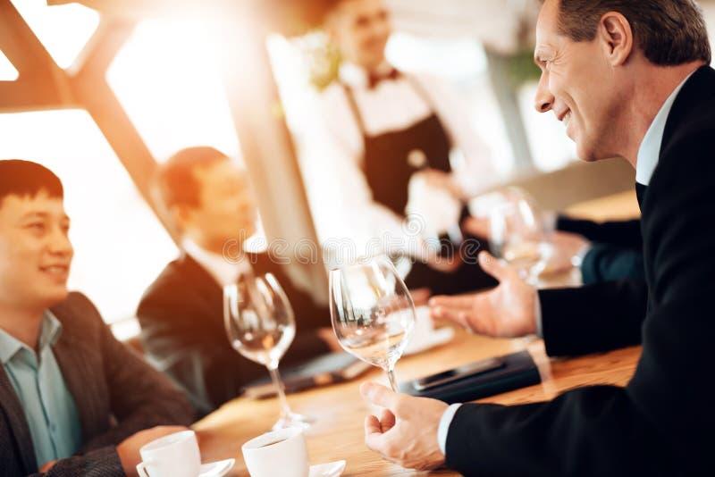 Encuentro con de hombres de negocios chinos en restaurante El camarero trae el vino fotos de archivo libres de regalías