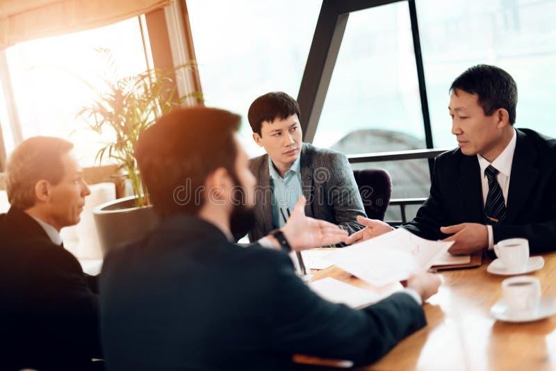 Encuentro con de hombres de negocios chinos en restaurante Están discutiendo el gráfico de negocio fotos de archivo
