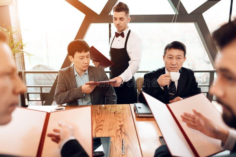 Encuentro con de hombres de negocios chinos en restaurante Los hombres están discutiendo su orden fotografía de archivo