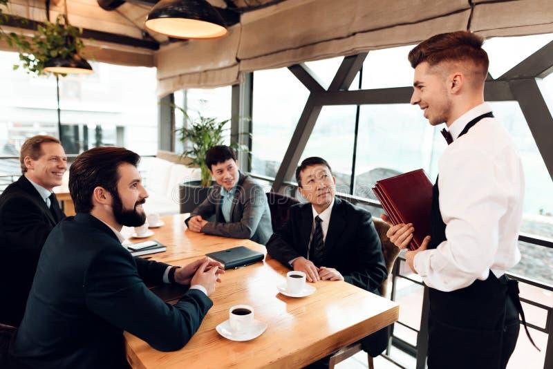 Encuentro con de hombres de negocios chinos en restaurante Los hombres están haciendo su orden fotografía de archivo