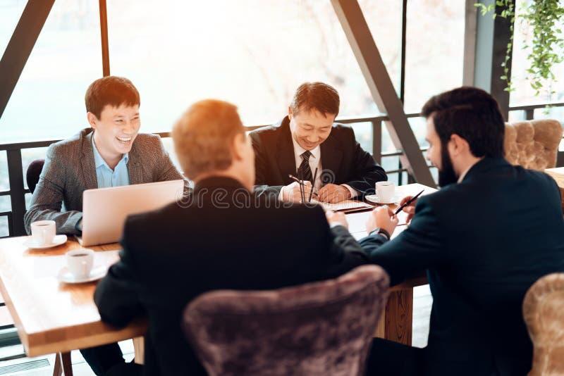 Encuentro con de hombres de negocios chinos en restaurante Los hombres laughting imágenes de archivo libres de regalías