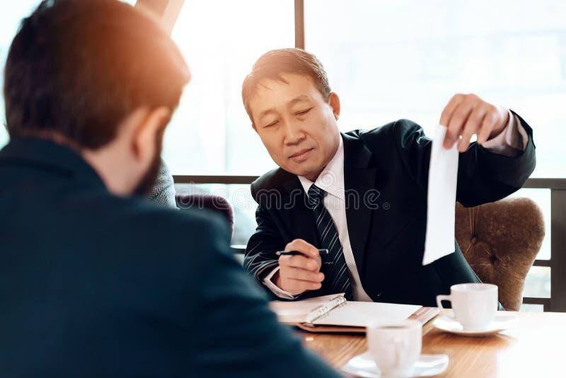 Encuentro con de hombres de negocios chinos en restaurante Se están sentando detrás de la tabla foto de archivo