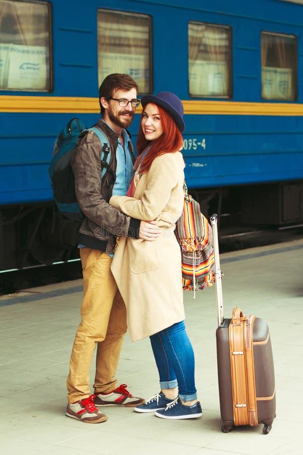 Encuentro después de un viaje de un par feliz que abraza en la calle en una estación de tren Luz del sol caliente de la tarde her fotografía de archivo