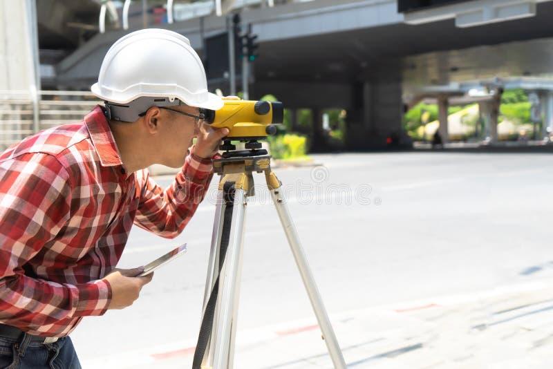 Encuesta sobre la tierra del ingeniero civil con el equipm del tacheometer o del teodolito imágenes de archivo libres de regalías