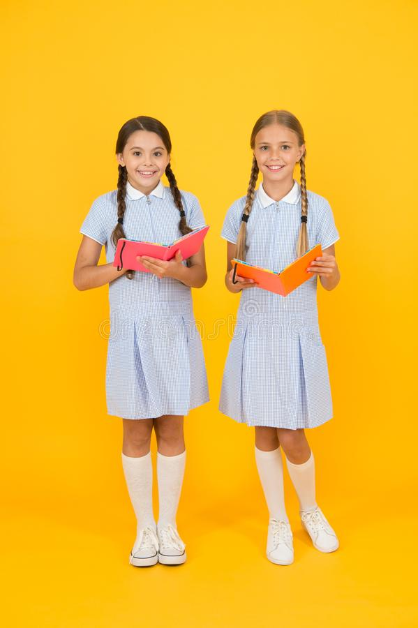 Encyclopedia book for children. small girls love literature. old school. happy friends in retro uniform. vintage kid. Fashion. back to school. small girls hold stock photo