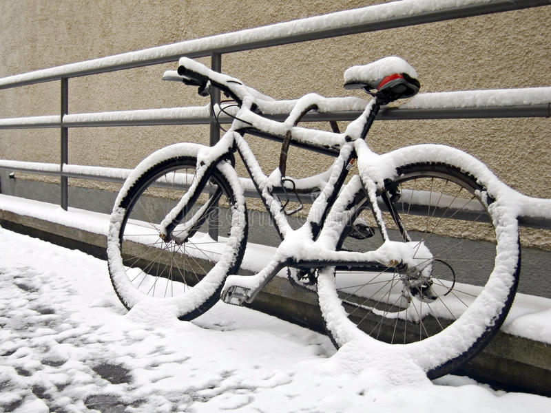 The end of bike season. (bike covered with snow royalty free stock photography