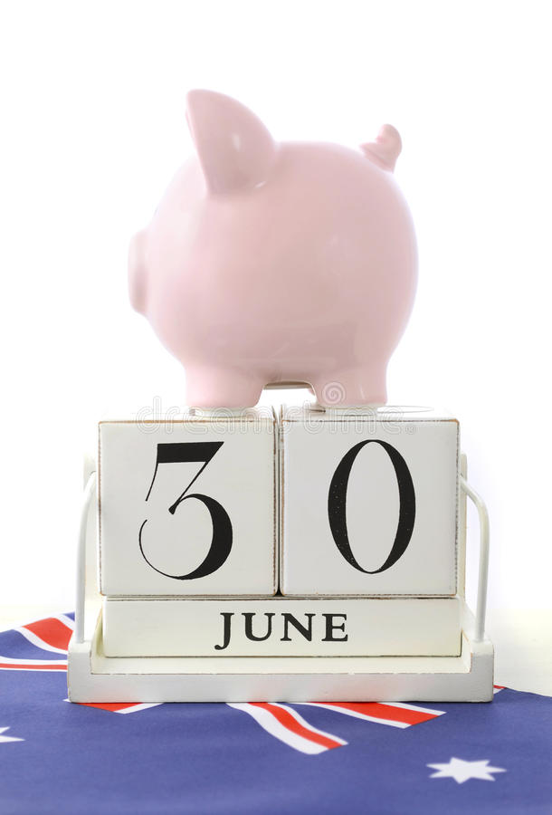End of Financial Year Savings Concept. With piggy bank and wood calendar and Australian Flag on white wood table royalty free stock photography