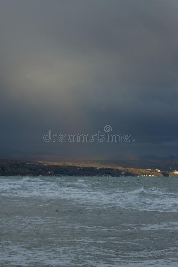 End of gale. Closing stormy date at the Black sea. Sunlight fell upon the Caucasus Mountains royalty free stock image
