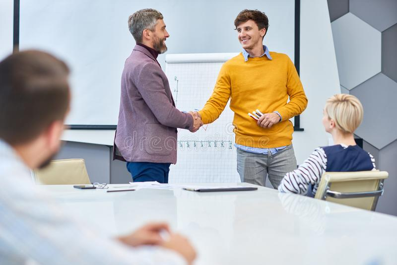 End of Marketing Meeting in Office. Portrait of young businessman presenting marketing report shaking hands with boss at the end of meeting royalty free stock images