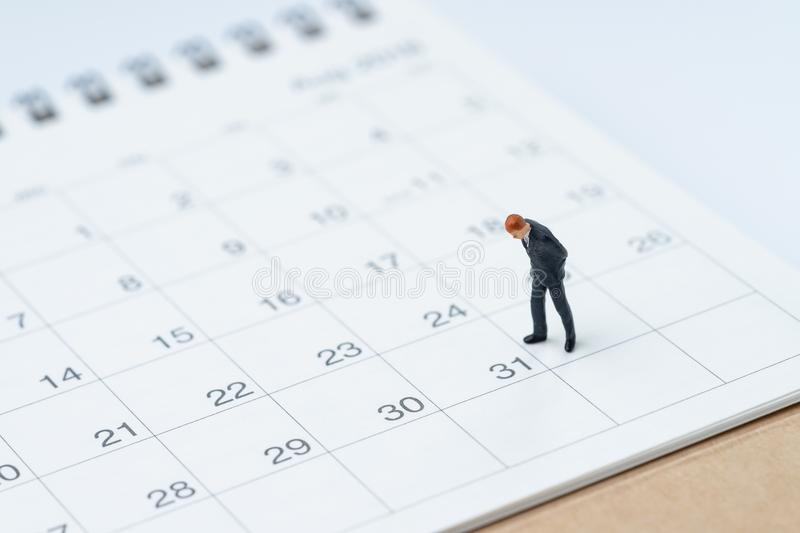 End of month for salary man concept, miniature people businessman office guy standing and looking at number 31 date, waiting to g stock images