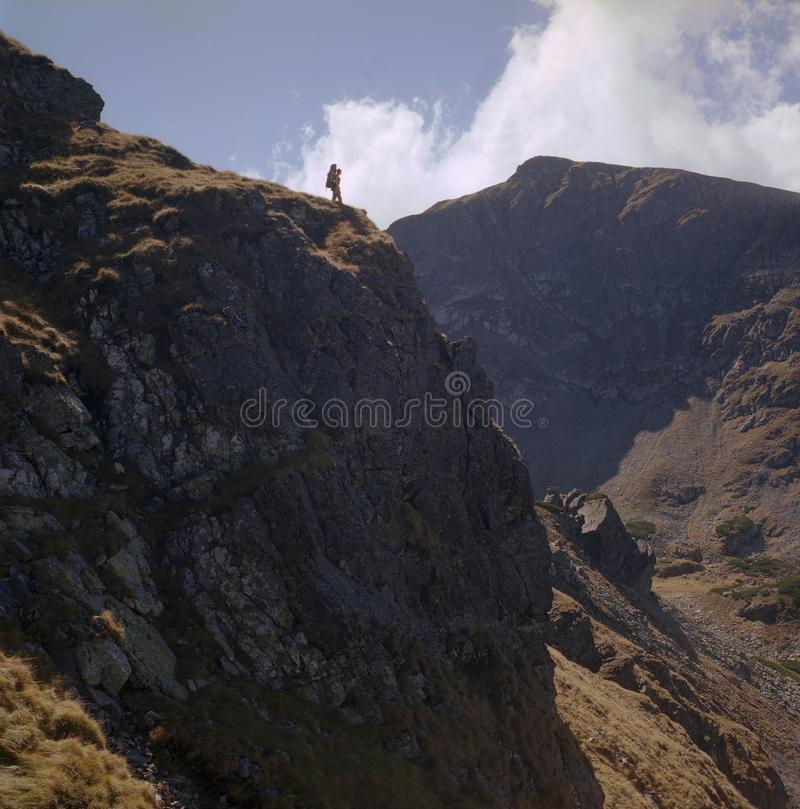 At the end of the mountain road. Man standing on edge of rock formation  in Parang mountains, Carpathians, Romania