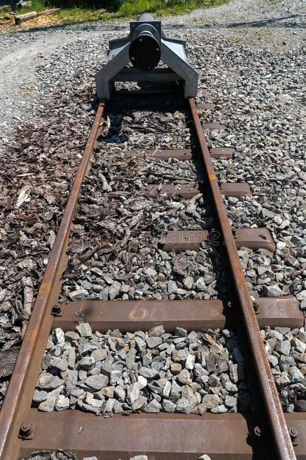 End of narrow gauge railroad track with a buffer stop royalty free stock photos