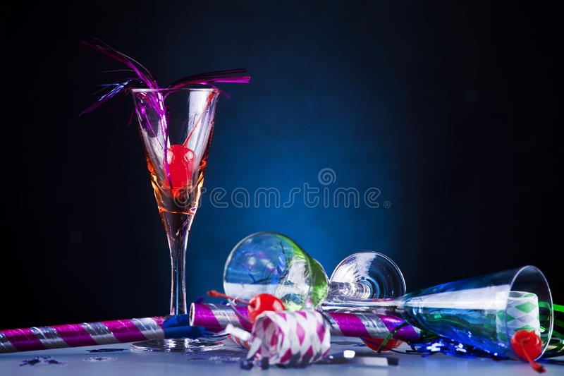 End of the party. A set of glasses and othe party stuff on a black and blue backgorund royalty free stock photo