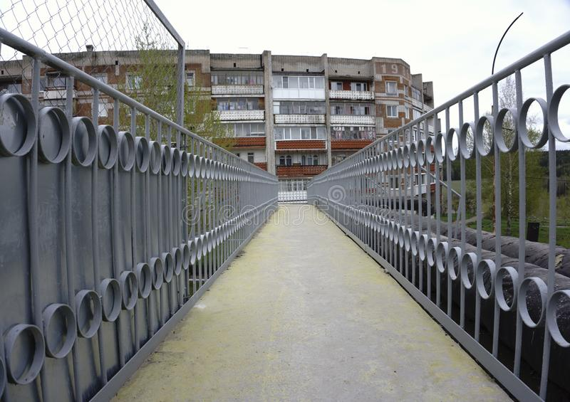 Pedestrian bridge over suburban road and curved continuation of wooded recreational trail. End of pedestrian bridge over suburban road and curved continuation of stock photo