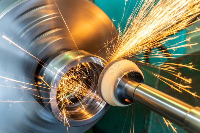 End processing of a metal surface with an abrasive stone on a circular grinding machine, sparks fly in different directions.  royalty free stock image
