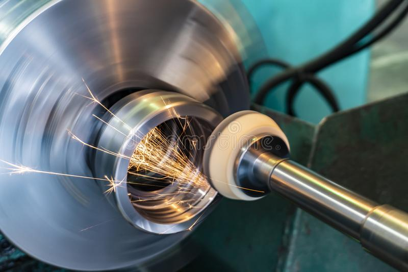 End processing of a metal surface with an abrasive stone on a circular grinding machine, sparks fly in different directions.  royalty free stock photo