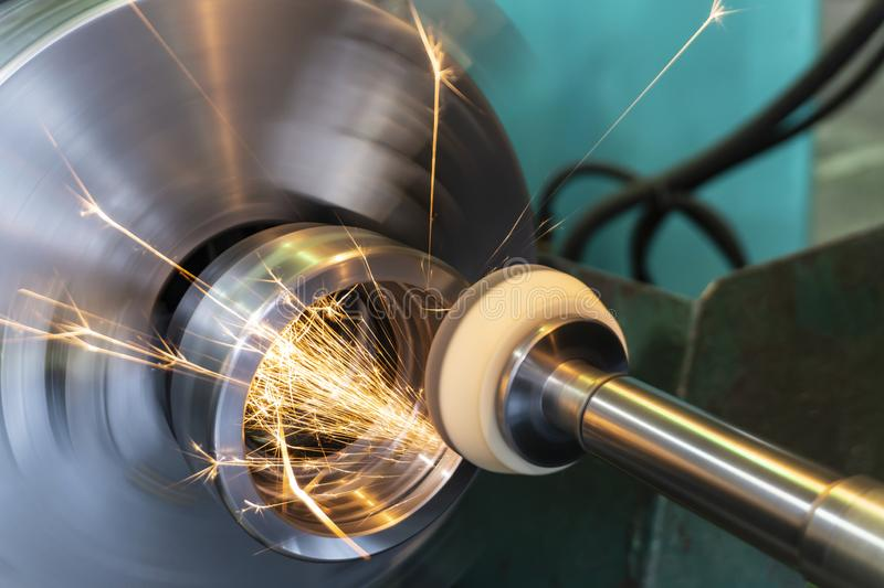 End processing of a metal surface with an abrasive stone on a circular grinding machine, sparks fly in different directions.  stock images