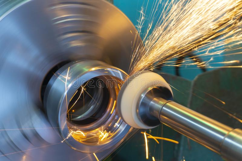 End processing of a metal surface with an abrasive stone on a circular grinding machine, sparks fly in different directions.  stock photos