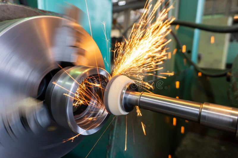 End processing of a metal surface with an abrasive stone on a circular grinding machine, sparks fly in different directions.  royalty free stock images
