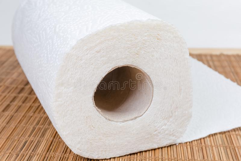 End roll of paper towels on bamboo table mat closeup. Roll of two-ply paper towels with tear-off sheets on the wooden bamboo table mat. View from the end roll stock photo