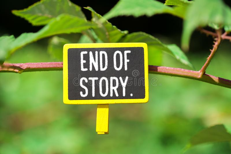 End of story text on board. End of story text written on yellow small chalkboard linked tree with clothespin on nature green background royalty free stock image
