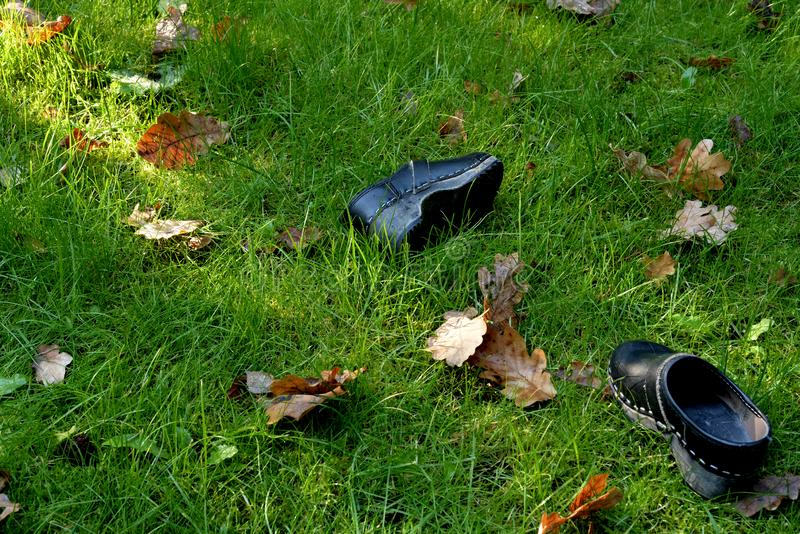Child`s clogs left in the garden. royalty free stock images
