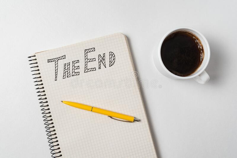 The end text on copybook. Notepad, pen and cup of coffee on white background. Top view stock photo