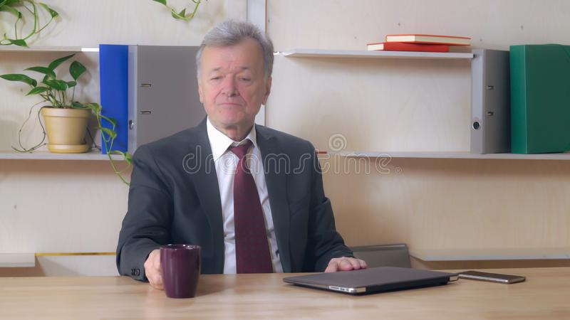 The end of the workday leader in years. Respectable business person finishing project closed laptop and enjoy tea at the office. Happy white leader sitting at stock photos