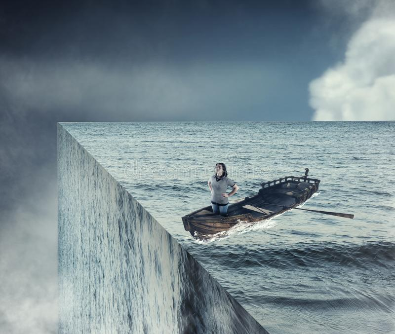 End of the world. Girl sail on a boat in the ocean royalty free stock photos