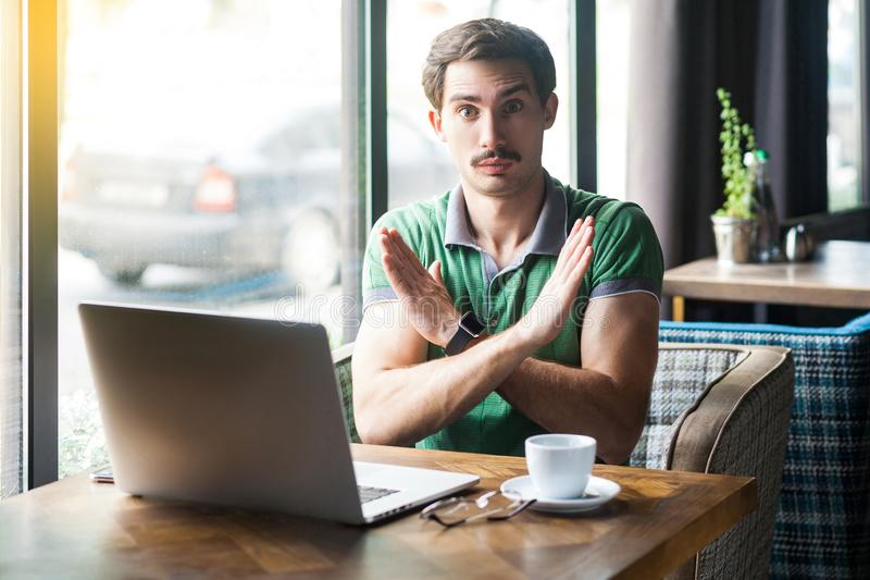 This is the end. Young serious businessman in green t-shirt sitting and looking at camera showing closed or x sign with hands. Business and freelancing concept royalty free stock photography