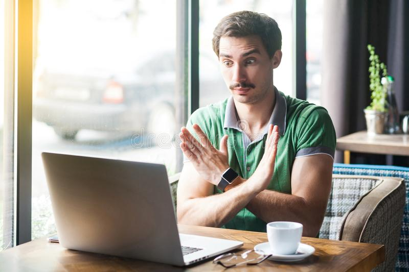 This is the end. Young serious businessman in green t-shirt sitting and looking at laptop screen on video call, showing closed or. X sign with hand. business royalty free stock photography
