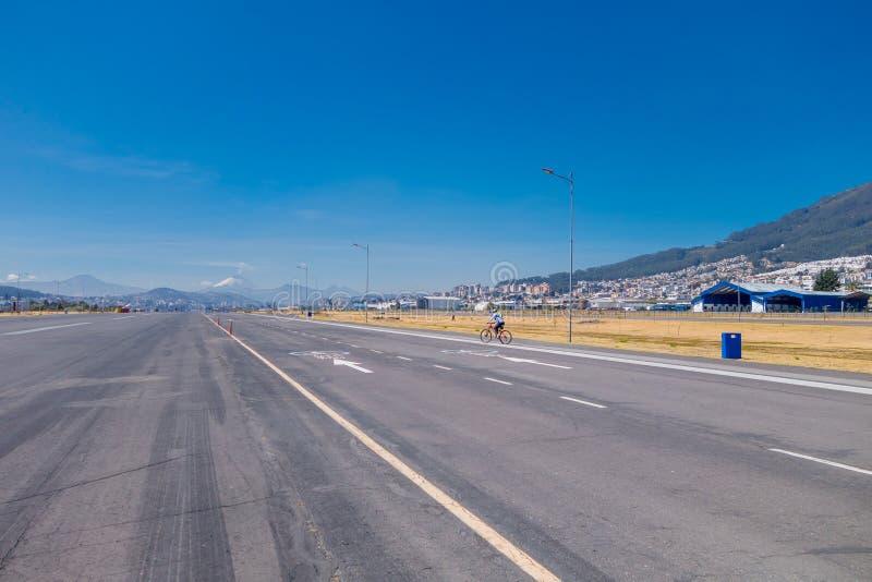 Am Ende der Straße erscheint Cotopaxi an einem sonnigen Tag, an der paviment Straße Radfahrer zur Schau tragen stockfoto