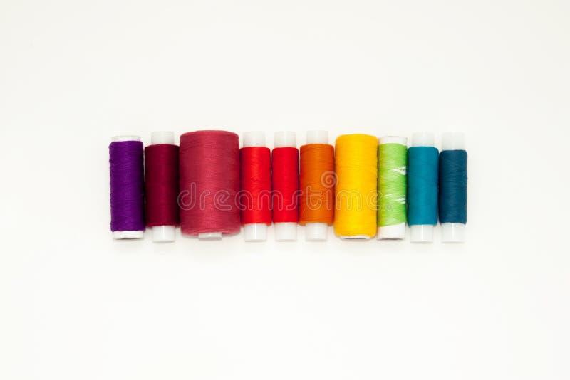 Endecha con los carretes coloridos del hilo del algod?n, hilado del bordado, bobinas del arco iris, mofa del plano para arriba, v imagenes de archivo