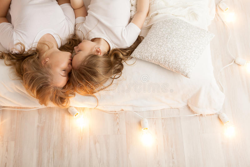 Endecha de la madre y de la hija en la cama y el beso Visión desde arriba togetherness Interior del desván foto de archivo