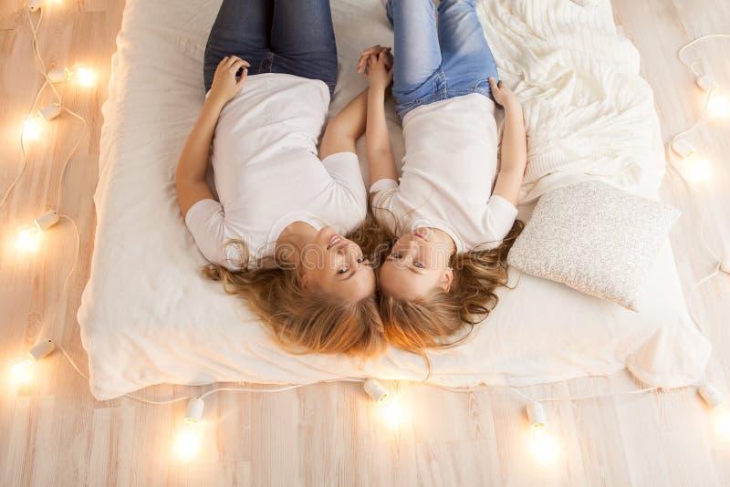 Endecha de la madre y de la hija en la cama y mirada en la cámara Visión desde arriba togetherness Interior del desván fotografía de archivo libre de regalías