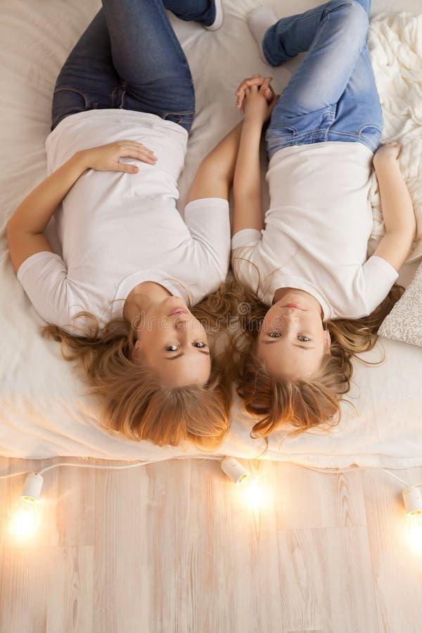 Endecha de la madre y de la hija en la cama y mirada en la cámara Visión desde arriba togetherness Interior del desván imagen de archivo libre de regalías