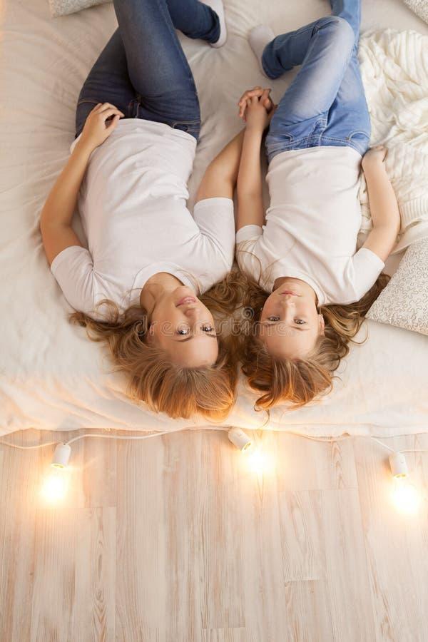 Endecha de la madre y de la hija en la cama y mirada en la cámara Visión desde arriba togetherness Interior del desván Copia-espa imagen de archivo libre de regalías