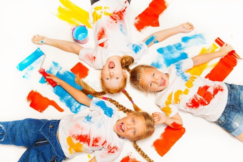 Endecha de tres niños en el piso y la risa imagenes de archivo