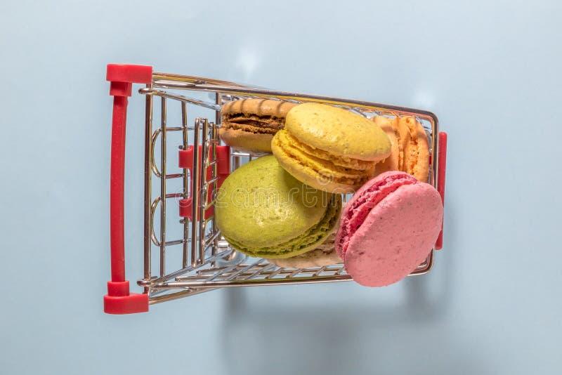 Endecha del Flt de la carretilla minúscula de las compras por completo de las galletas coloridas de los macarons fotos de archivo