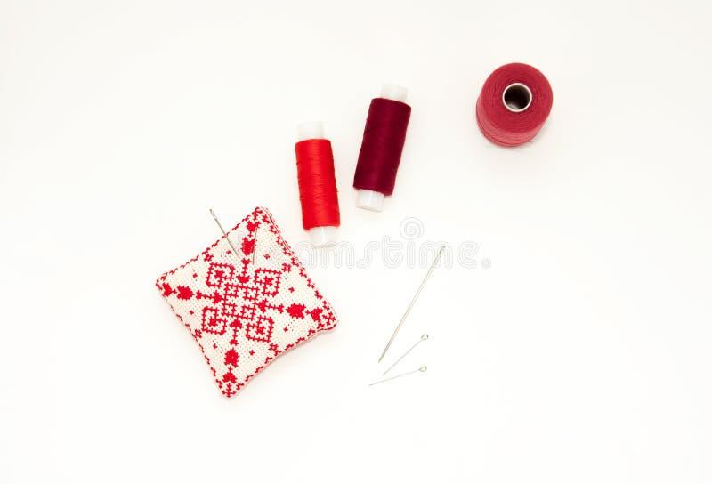 Endecha del plano con el coj?n bordado rojo hecho a mano de la aguja, carretes del hilo, pernos, agujas, mofa para arriba, visi?n fotos de archivo