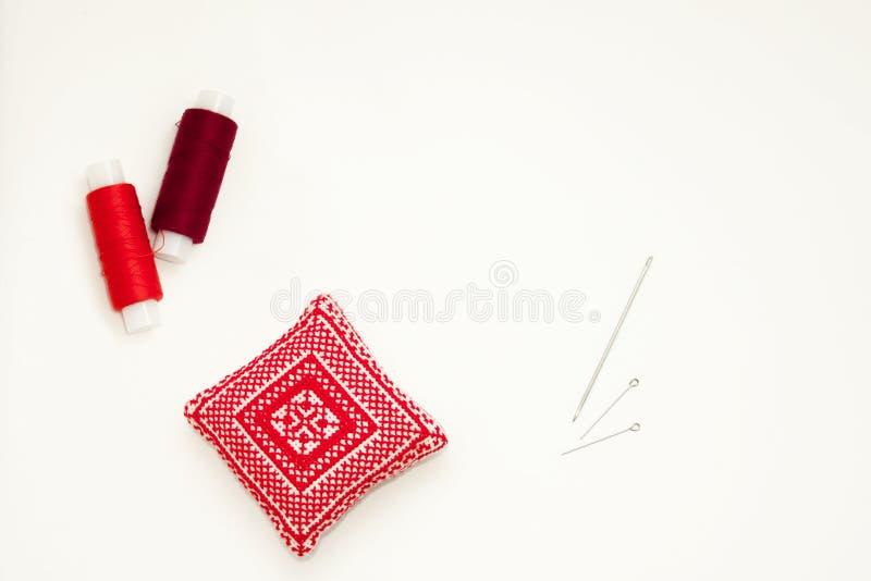 Endecha del plano con el coj?n bordado rojo hecho a mano de la aguja, carretes del hilo, pernos, agujas, mofa para arriba, visi?n foto de archivo