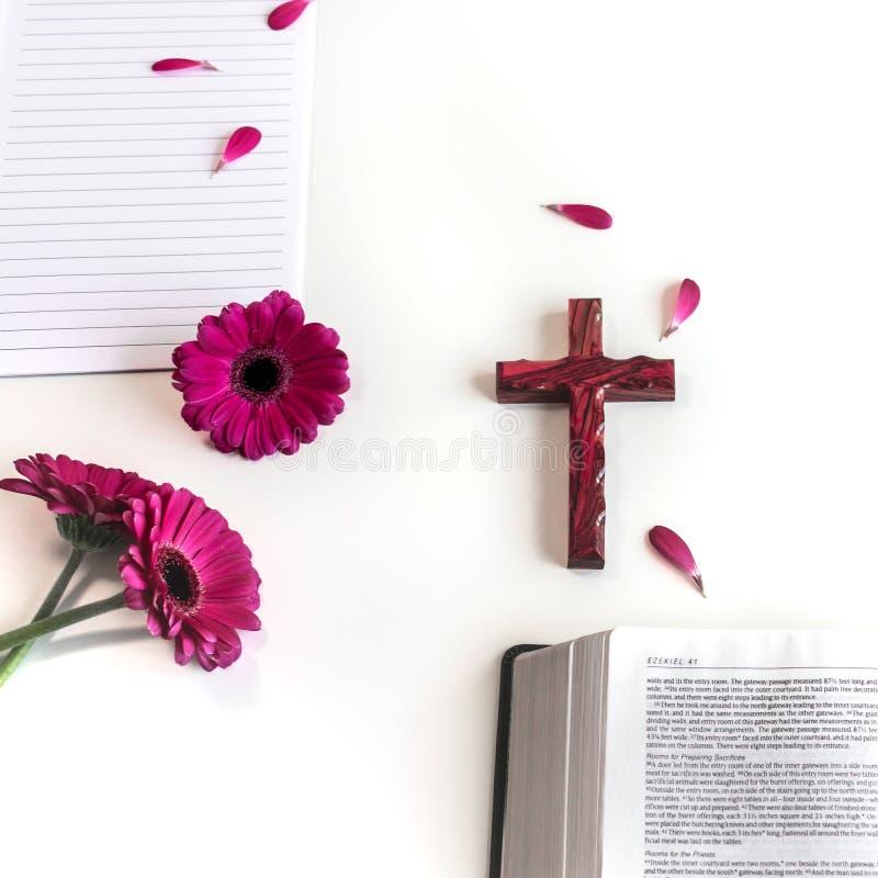 Endecha plana: biblia abierta, libro, cruz de madera y rosa, púrpuras, violette, flor roja del Gerbera con los pétalos imágenes de archivo libres de regalías