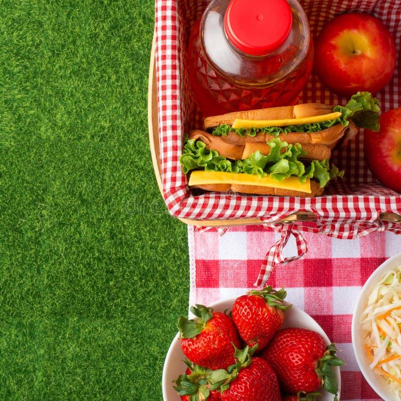 Endecha plana Comida campestre en el c?sped con un velo, una cesta, bocadillos, fresas, un jugo y una comida fresca de la ensalad imagen de archivo