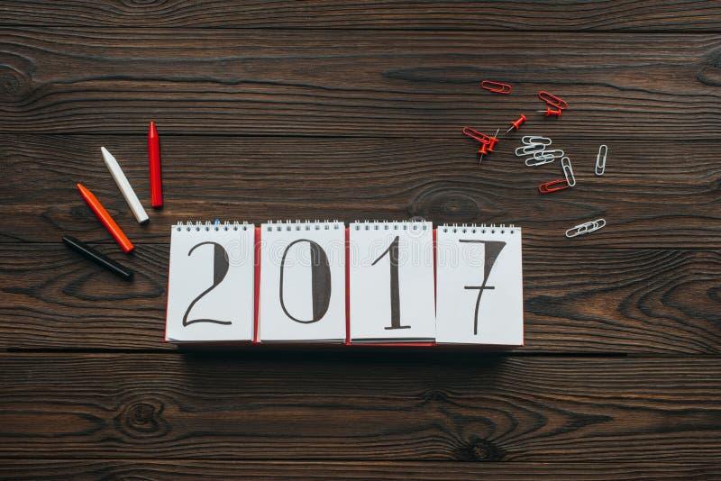 endecha plana con el arreglo del calendario 2018, de lápices, de pernos y de clips en oscuridad ilustración del vector