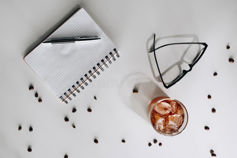 endecha plana con el vidrio del café helado frío, de los granos de café asados, de las lentes, del cuaderno vacío y de la pluma imagen de archivo