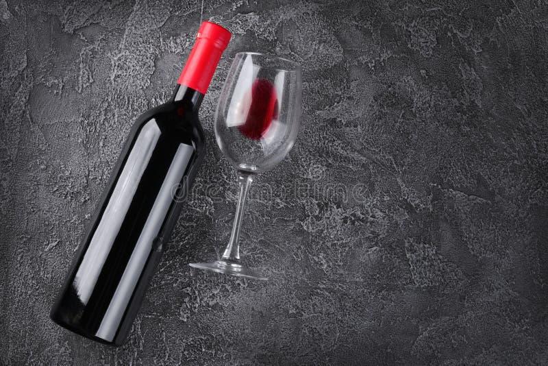 Endecha plana con la botella y el vidrio de vino rojo de mentira para probar imágenes de archivo libres de regalías